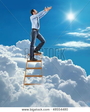 young confident businessman standing at the ladder high in the sky pulls hands to the sky