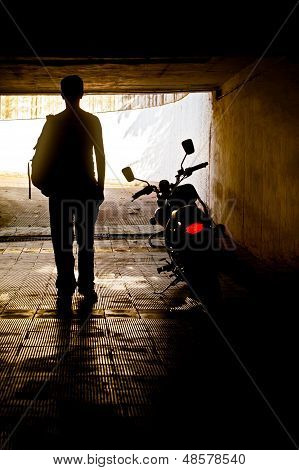 Man In Dark Tunnel Near Motorbike