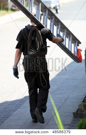 Chimney Sweep Carrying An Extension Ladder
