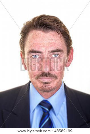 Attractive middle aged business man with intense blue eyes. Studio shot over white with selective focus to accentuate the face