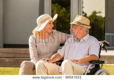 Senior disabled man and wife talking outdoors in park