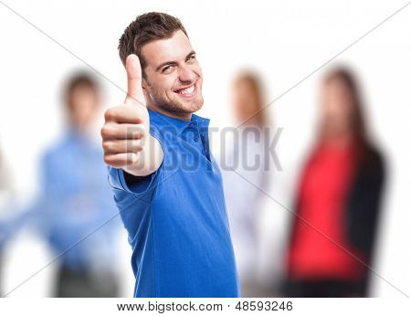 Handsome young man doing thumbs up in front of a group of people