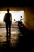 Vertical silhouette concept capture of a man in a vest with ruck sack back pack near his motorcycle which has its tail slights switched  on in a tunnel poster