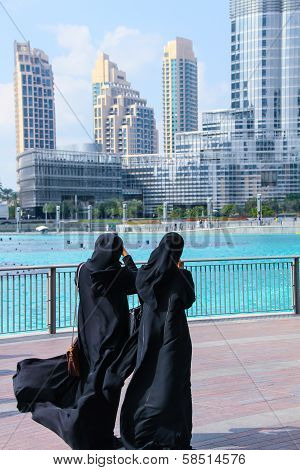 Dubai in January. Two Arab women near the tallest building in the world Burj Khalifa