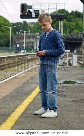 Youth Texting At Railway Station