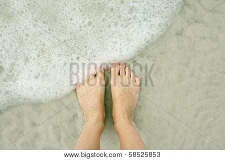 Woman's Feet In Ocean On Beach