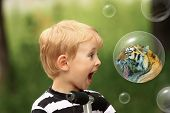 The blond guy surprised by a tiger in a bubble. Other bubbles are on a green background. poster
