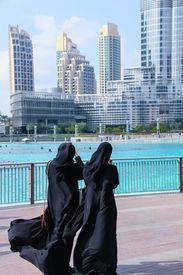 Dubai in January. Two Arab women near the tallest building in the world Burj Khalifa