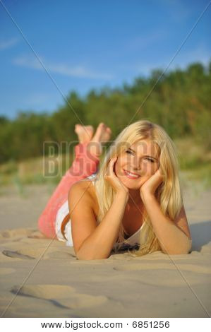 Young beautiful summer woman relaxing on a beach