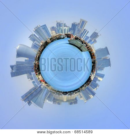 The port of Doha, Qatar and cityscape in a 360 degree circumference around a mini planet with the modern skyscrapers on a sunny skyline and a cruise ship in the sea , floating in a blue sky