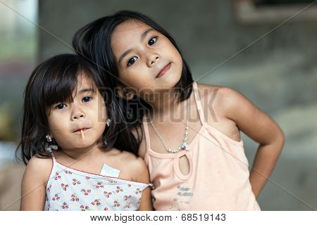 SIQUIJOR ISLAND, PHILIPPINES, DECEMBER 21, 2013: Two unidentified Filipino little girl sisters posing in front of her home in north Siquijor island, Philippines.
