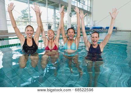 Female fitness class doing aqua aerobics and cheering in swimming pool at the leisure centre