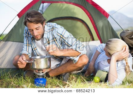 Attractive happy couple cooking on camping stove on a sunny day poster