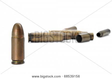 a bullet and a pile of bullet shells on a white background