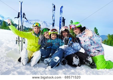 Smiling friends after skiing sit on snow together