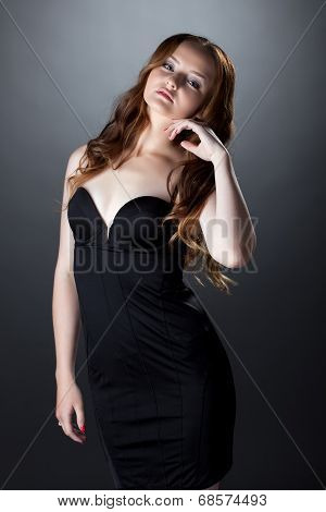 Languid red-haired girl posing in skin-tight dress