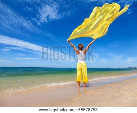 Beautiful Young Woman Holding Yellow Fabric On Wind
