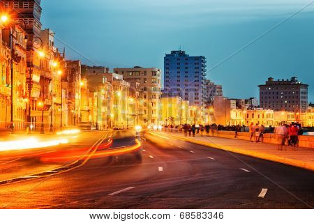 Sunset in Old Havana with  the street lights of El Malecon and light trails from the passing cars