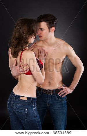 Lusty Couple Standing Over Black Background