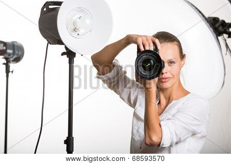 Pretty, female pro photographer with digital camera - DSLR and a huge telephoto lens in her well equiped studio, taking photos (color toned image; shallow DOF)