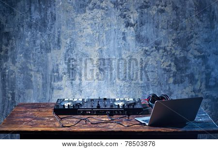 Dj mixer with headphones and laptop on wooden table close-up.
