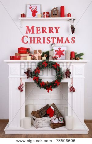 Decorations with Merry Christmas inscription on mantelpiece on wooden floor and  white wall background