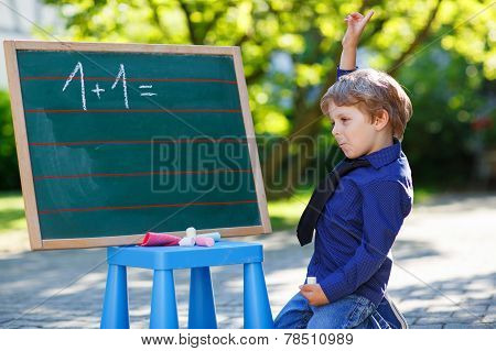 Cute little child at blackboard practicing mathematics outdoor school or nursery. poster
