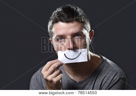 Young Depressed Man Lost In Sadness And Sorrow Holding Paper With Smiley On His Mouth In Depression