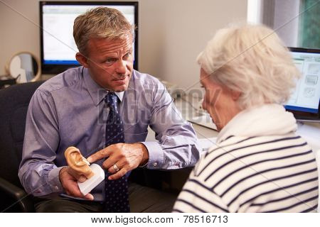 Doctor Showing Senior Female Patient Model Of Human Ear