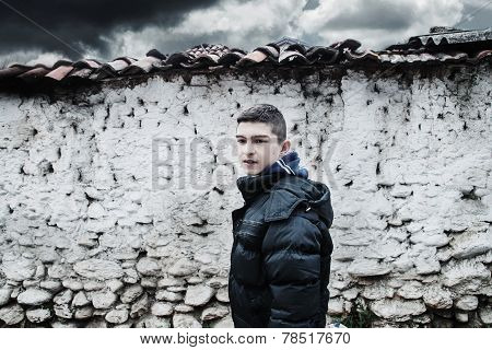 sad young boy before loam wall