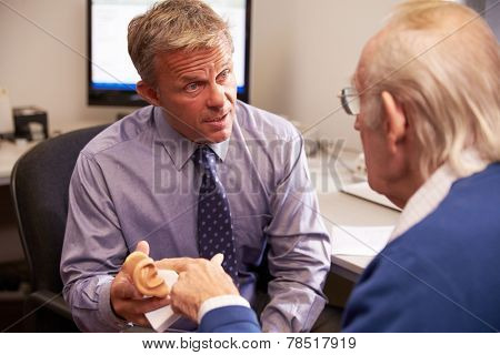 Doctor Showing Senior Male Patient Model Of Human Ear