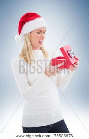 Disappointed blonde opening christmas gift on vignette background