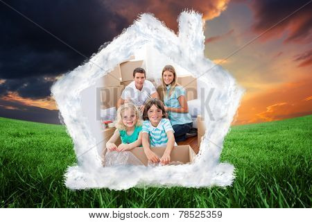 Smiling family packing boxes against green field under orange sky