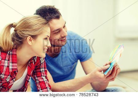 repair, interior design, building, renovation and home concept - smiling couple looking at color samples at home