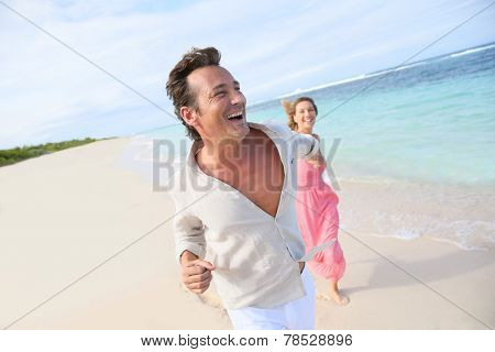 Couple having fun running on a caribbean beach