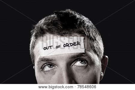 Young Man With Blue Eyes And Tape Text Out Of Order On Forehead In Dry Empty Mind