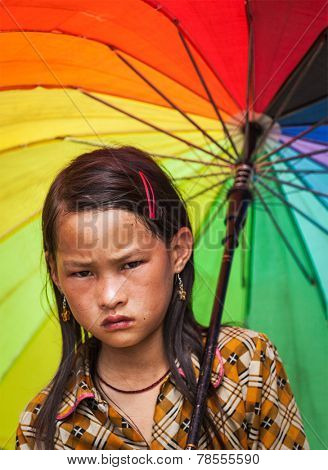 SAPA, VIETNAM - JUNE 10, 2011: Unidentified vietnamese girl with umbrella in Ta Van village. Though Vietnam's economic growth rate is among the highest in the world, poverty rate is still high