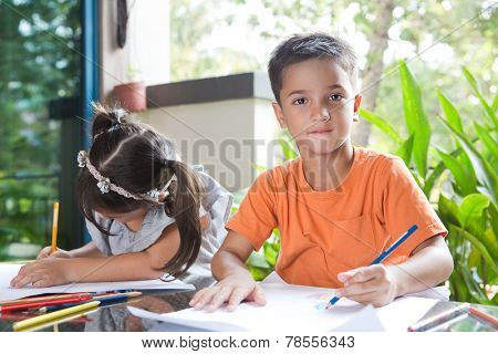Cute little pan asian boy smiling while holding a color pencil sitting next to his younger sister engross in her coloring activity in home environment