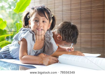 CuteÃ?Â??little pan asian girl smiling with a story book sitting next to an older brother engrossed in coloring activity in home environment