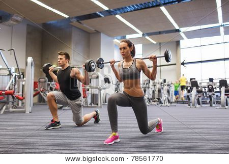 sport, bodybuilding, lifestyle and people concept - young man and woman with barbell flexing muscles and making shoulder press lunge in gym poster