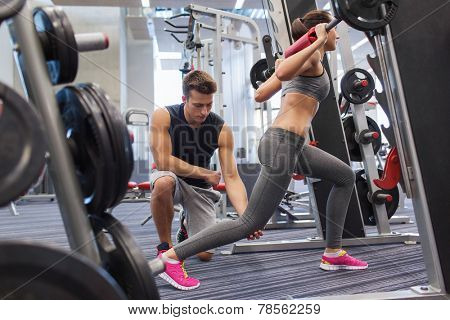 sport, fitness, teamwork, weightlifting and people concept - young man and personal trainer with barbell flexing muscles in gym
