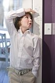 Boy checking height on growth chart at home on doorframe poster