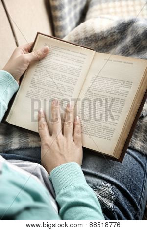 Young woman reading book, close-up, on home interior background