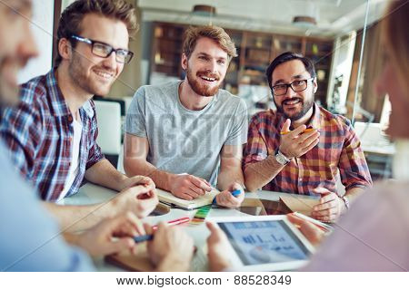 Group of male employees talking to co-worker