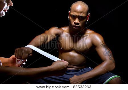 Motivated MMA fighter or Boxer with trainer applying athletic tape poster