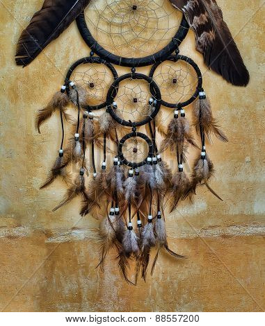 Dream Catcher With Eagle And Raven Feathers On Orange Structure Wall