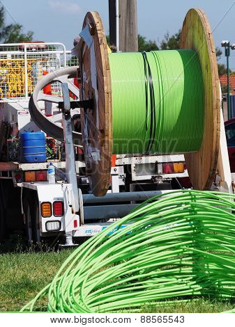 Green fiber optic cable piled up behind an installation truck