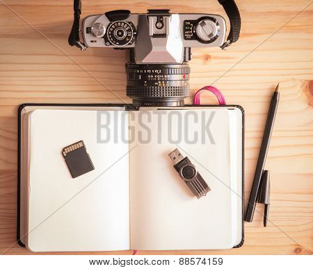 Retro Vintage Old Photo Camera With Notebook, Pen, Pendrive, Sd Card And Mouse On A Wooden Table