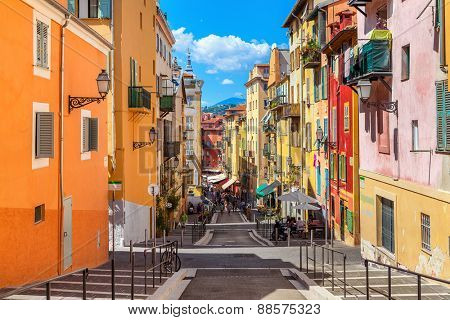 NICE, FRANCE - AUGUST 23, 2014: Narrow street in old tourist part of Nice - fifth most populous city and one of the most visited cities in France, receiving 4 million tourists every year.