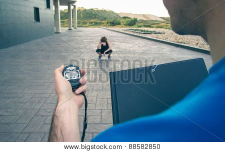 Trainer hand using chronometer to timing woman training